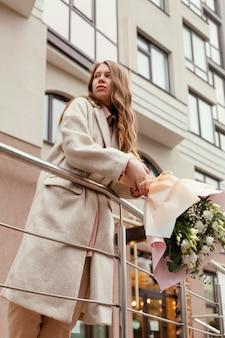 Kobieta trzyma bukiet kwiatów na zewnątrz w mieście