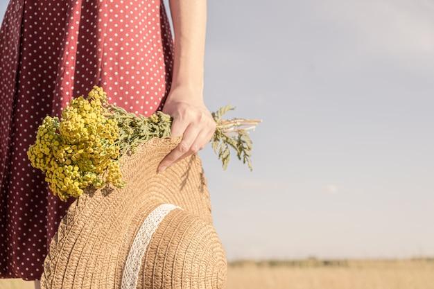 Kobieta trzyma bukiet kwiatów pola i kapelusz. scena wiejska: zbliżenie kobiety w sukience w groszki z kapeluszem rolnika i bukietem w dłoni