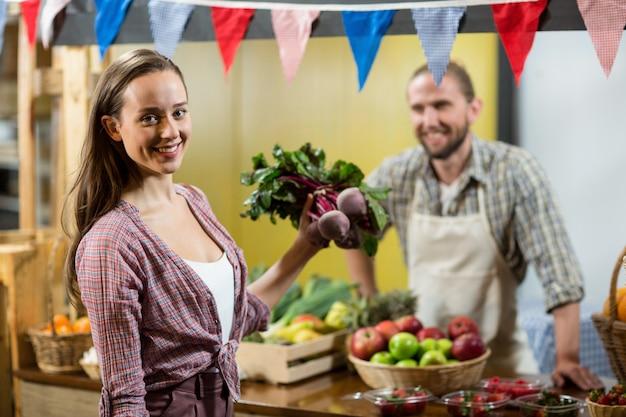 Kobieta trzyma buraki przy ladzie w sklepie spożywczym
