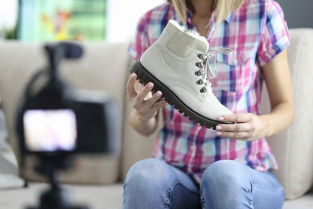 Kobieta trzyma but w dłoniach i przegląda aparat