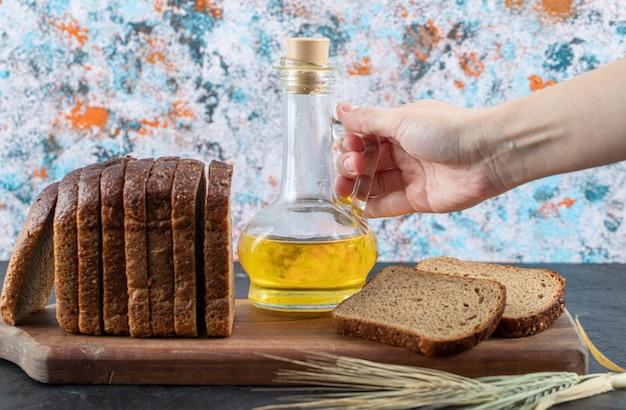 Kobieta trzyma butelkę oleju na marmurowym stole z kromkami chleba.