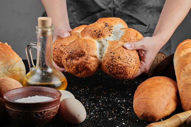 Kobieta trzyma chleb na ciemnym stole z jajkami, miską mąki i szklanką oleju.