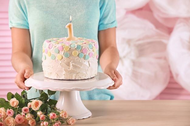 Kobieta trzyma ciasto ze świeczką na pierwsze urodziny, zbliżenie