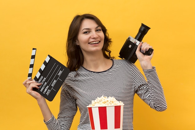 Kobieta trzyma clapperboard i kamery filmowej