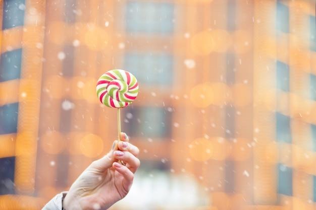 Kobieta trzyma cukierki karmelowe podczas opadów śniegu. miejsce na tekst