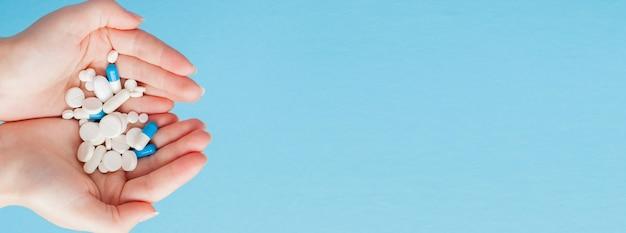 Kobieta trzyma cupped rękę pełną pigułek, widok z góry