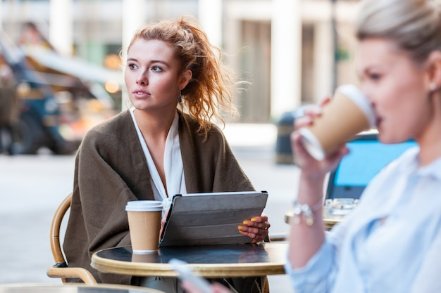 Kobieta trzyma cyfrową pastylkę i patrzeje daleko od przy kawiarnią w londyn