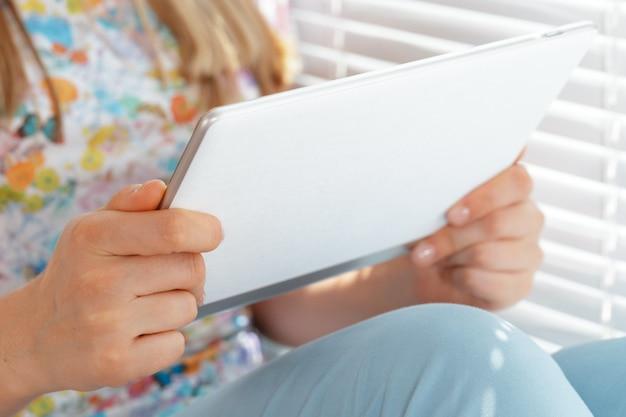 Kobieta trzyma cyfrową pastylkę, zbliżenie