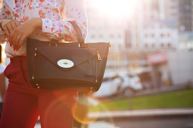 Kobieta trzyma czarną skórzaną torebkę spaceru po mieście. miejsce na tekst