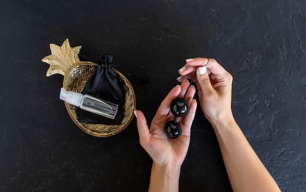 Kobieta trzyma czarne kulki dopochwowe gotowe do ćwiczeń mięśni. silne mięśnie pochwy