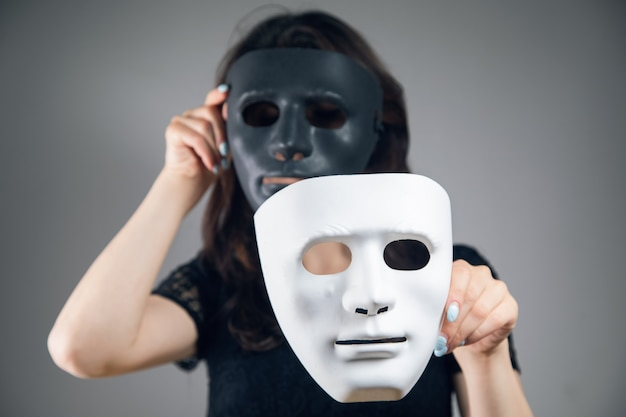 Kobieta trzyma czarno-białą plastikową maskę na szarym tle