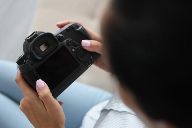 Kobieta trzyma czarny aparat w jej ręce zbliżenie