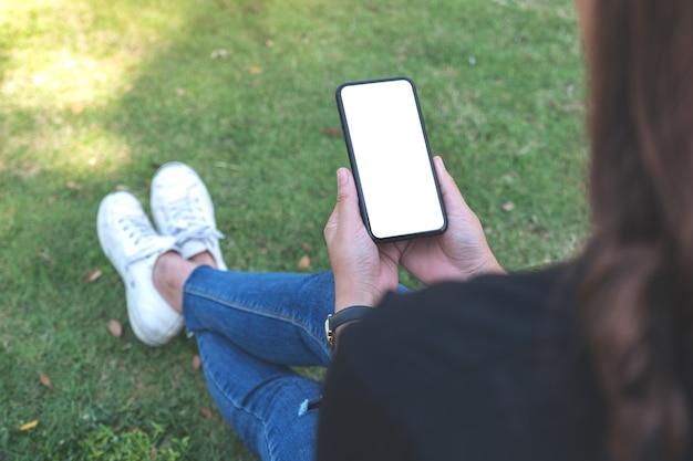 Kobieta trzyma czarny telefon komórkowy z pustym białym ekranem, siedząc w parku