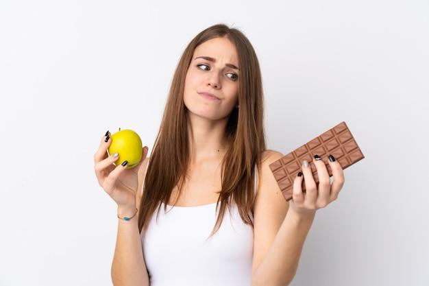 Kobieta trzyma czekoladę i jabłko na izolowane ściany