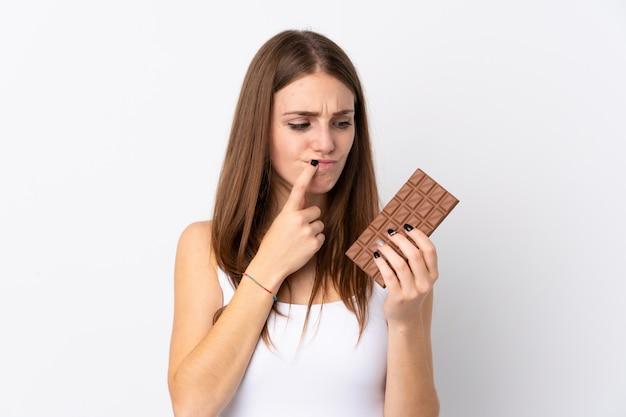 Kobieta trzyma czekoladę na białej ścianie