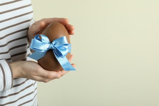 Kobieta trzyma czekoladowe jajko z niebieską wstążką, miejsca na tekst