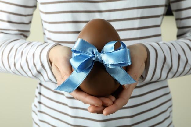 Kobieta trzyma czekoladowe jajko z niebieską wstążką, z bliska
