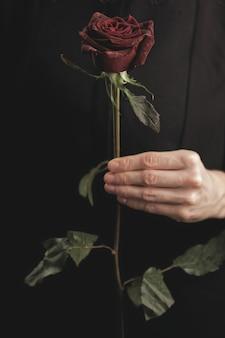 Kobieta trzyma czerwoną różę
