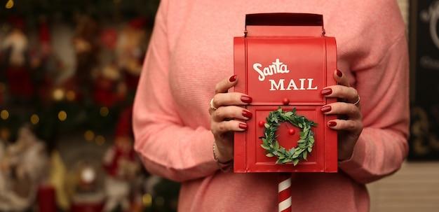 Kobieta trzyma czerwoną skrzynkę pocztową na listy do świętego mikołaja na tle bożego narodzenia