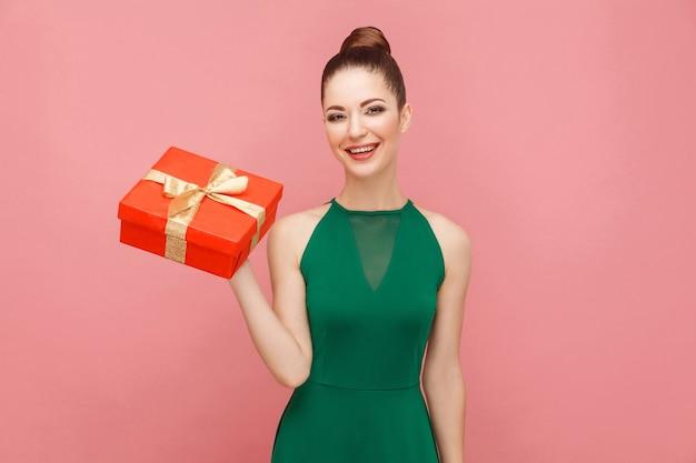 Kobieta trzyma czerwone pudełko i uśmiechnięty ząb