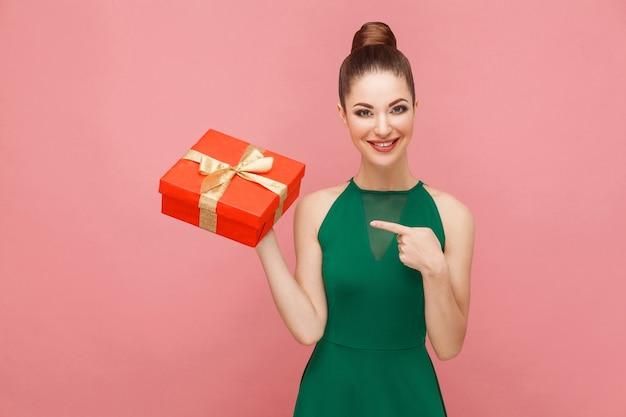 Kobieta trzyma czerwone pudełko i wskazując palcem