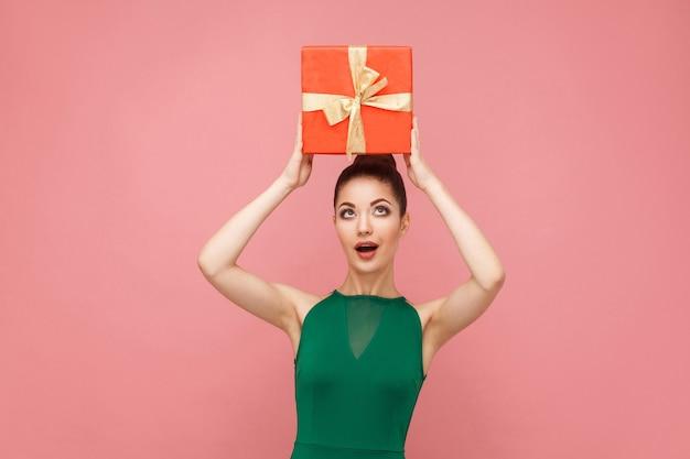Kobieta trzyma czerwone pudełko na głowie