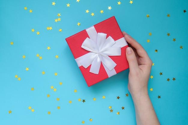 Kobieta trzyma czerwone pudełko na kolor niebieski ściany z rozrzuconych złotych gwiazd. świąteczna kartka z pozdrowieniami. koncepcja wakacje.