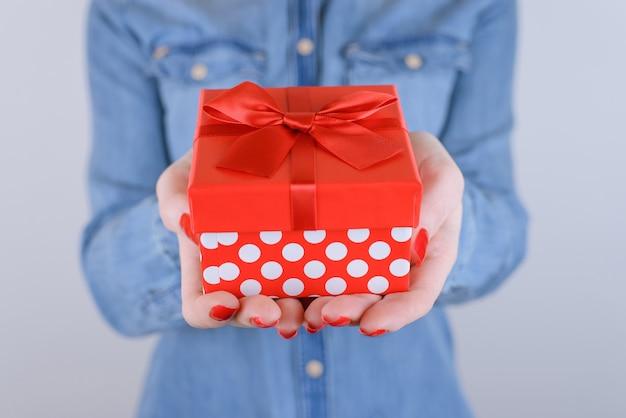 Kobieta trzyma czerwone pudełko na na białym tle szarym tle