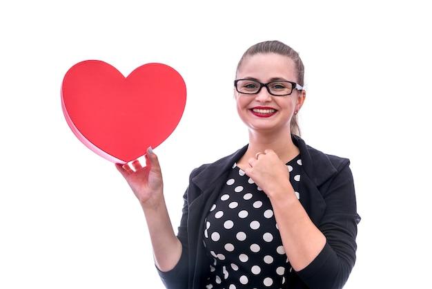 Kobieta trzyma czerwone serce i uśmiecha się na białym tle