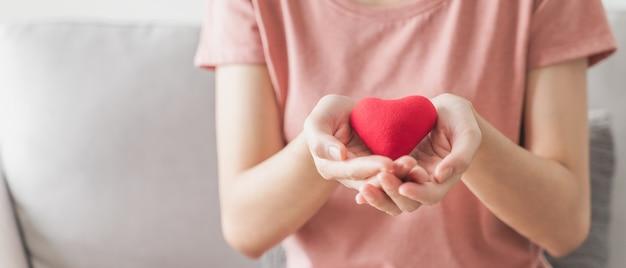 Kobieta trzyma czerwone serce miłość ubezpieczenie zdrowotne darowizna szczęśliwa organizacja charytatywna wolontariusz zdrowia psychicznego
