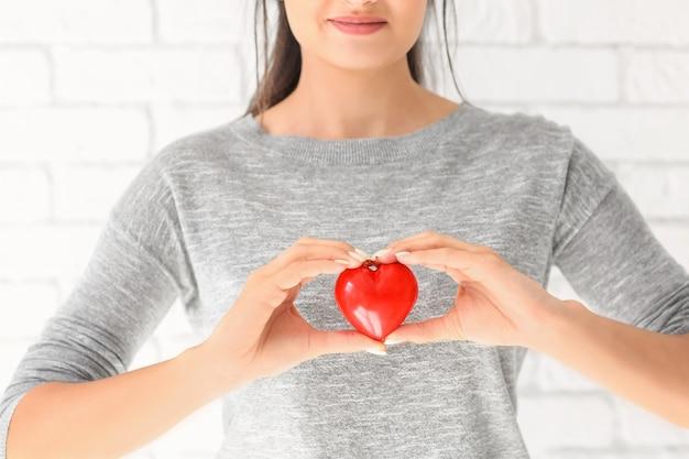 Kobieta trzyma czerwone serce na jasnej powierzchni. pojęcie opieki zdrowotnej