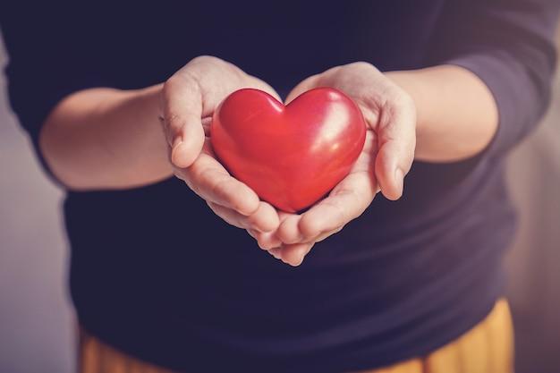 Kobieta trzyma czerwone serce, ubezpieczenie zdrowotne, darowizny, koncepcja wolontariatu charytatywnego
