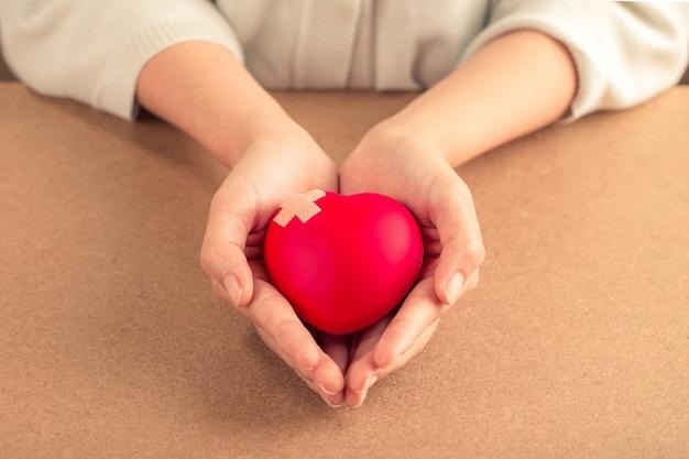 Kobieta trzyma czerwone serce z bandażem na podłoże drewniane. koncepcja opieki zdrowotnej.