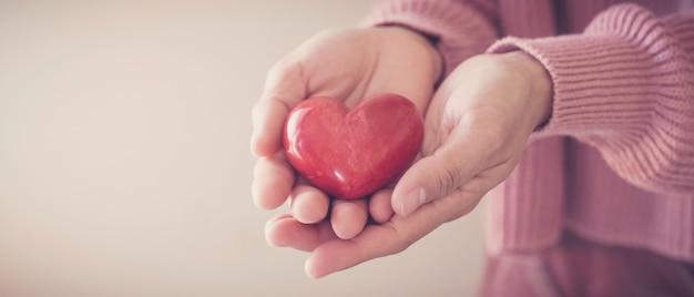 Kobieta trzyma czerwone serce