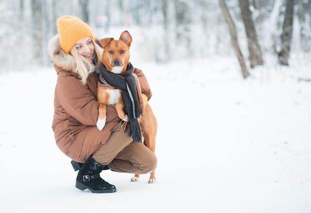 Kobieta trzyma czerwony kundel psa w szalik w zimowym lesie