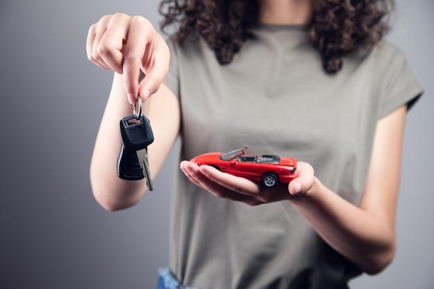 Kobieta trzyma czerwony model samochodu z kluczem