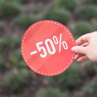 Kobieta trzyma czerwony znak sprzedaży