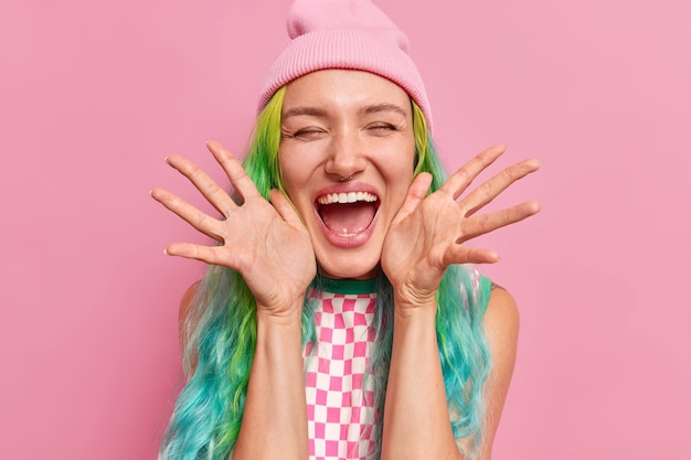Kobieta trzyma dłonie na boki przy twarzy śmieje się szczęśliwie czuje się bardzo szczęśliwa ma zamknięte oczy szeroko otwarte usta nosi kapelusz i sukienkę odizolowane na różowo