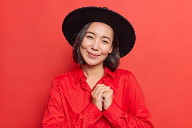 Kobieta trzyma dłonie ściśnięte blisko serca czuje się poruszona i zadowolona uśmiecha się delikatnie do kamery nosi czarny kapelusz koszula stoi na żywej czerwieni