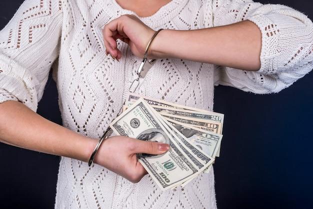 Kobieta trzyma dolary w kajdankach