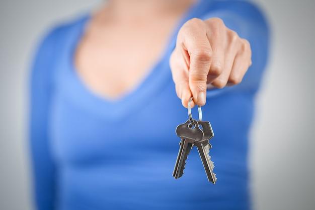 Kobieta trzyma domowych klucze przed jej ciałem. skoncentruj się na pierwszym planie
