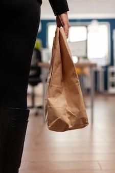 Kobieta trzyma dostawę jedzenie na wynos posiłek zamów papierową torbę podczas lunchu na wynos
