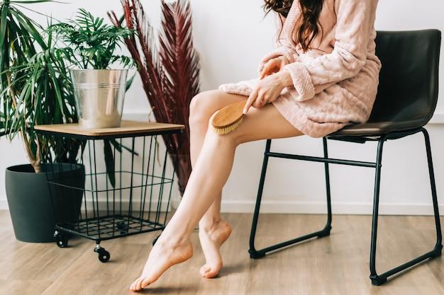 Kobieta trzyma drewnianą szczotkę i robi suchy masaż stóp