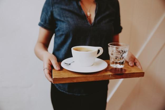 Kobieta trzyma drewnianą tacę z kawą i gazowaną wodą