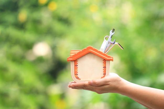 Kobieta trzyma drewniane dom i narzędzia budowlane