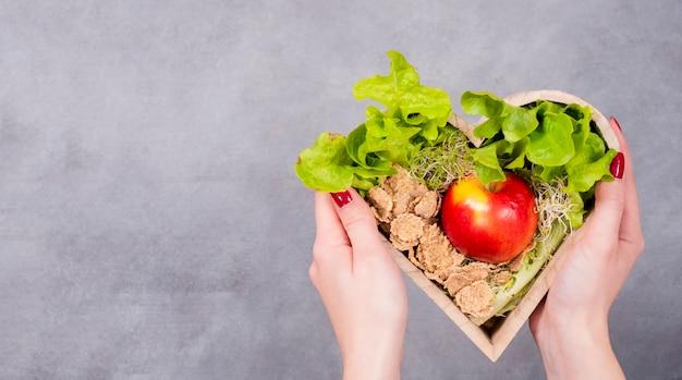 Kobieta trzyma drewnianego serce z jabłkiem i zbożami