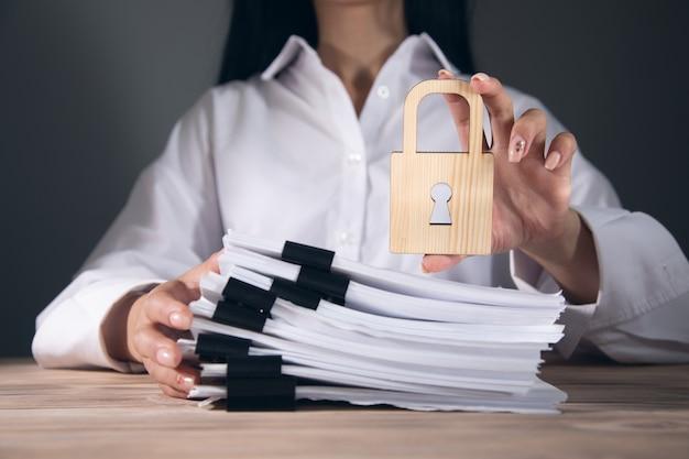 Kobieta trzyma drewniany zamek i dokumenty.