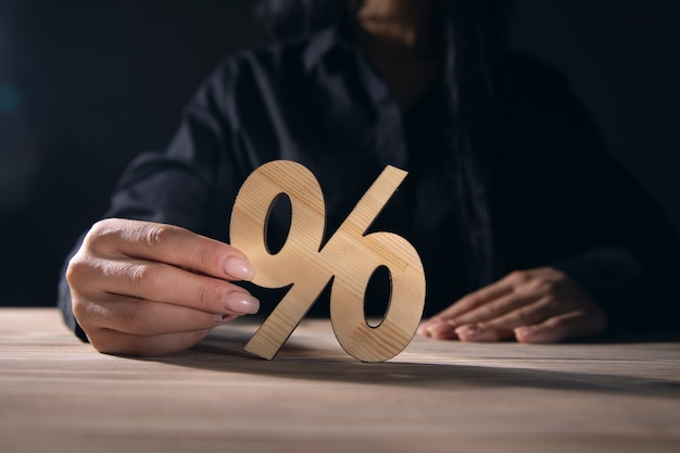 Kobieta trzyma drewniany znak procentu na tle stołu