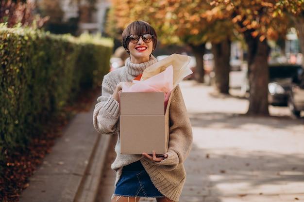 Kobieta trzyma dużą paczkę i idzie ulicą