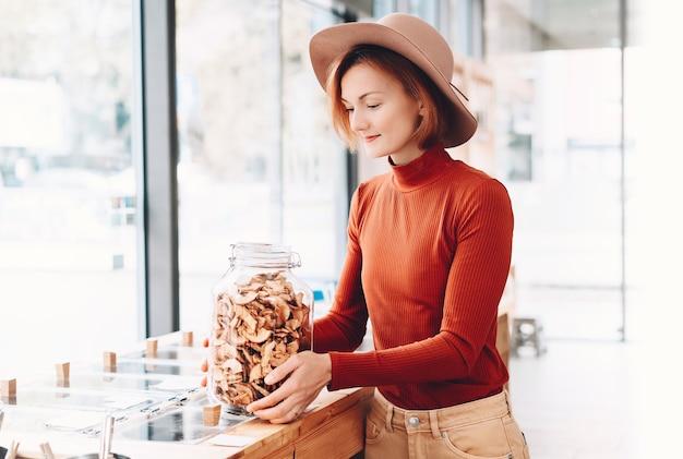 Kobieta trzyma duży szklany słoik z artykułami spożywczymi w plastikowym darmowym sklepie spożywczym sklep zero waste